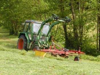 Bauer beim Heuwenden - Urlaub auf dem Bauernhof
